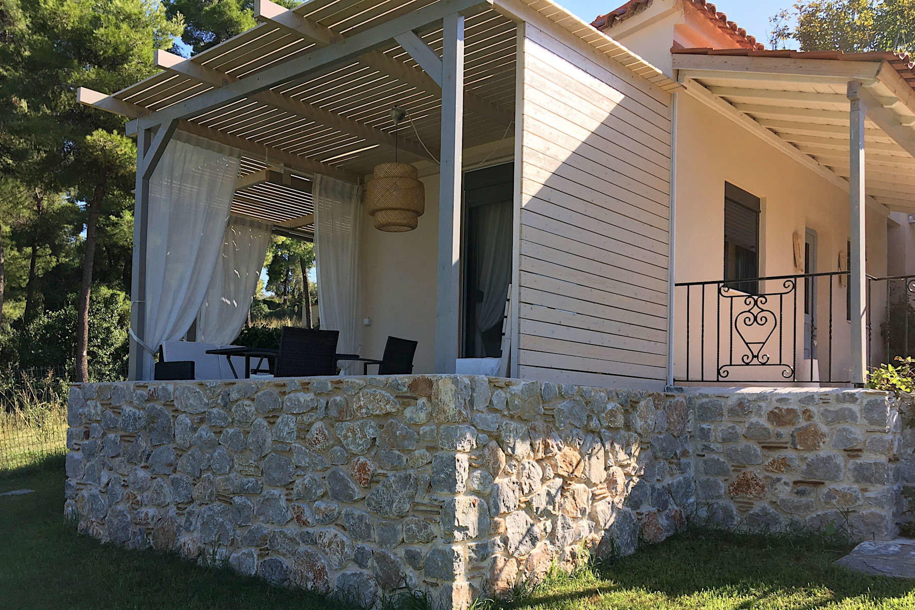 The ideal Greek island bungalow overlooking the garden lawn, pine trees and a superb, unobstructed view of the Aegean Sea, it is all you could ask for.